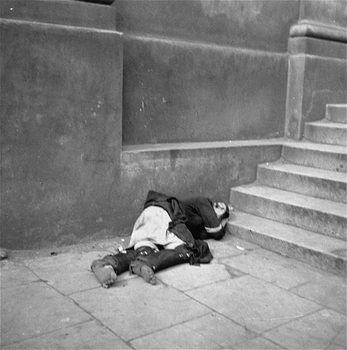 "The body of a dead woman on the street in the Warsaw ghetto.    Joest's caption reads: ""This woman must be dead.  I observed her for a long time and she did not move."""