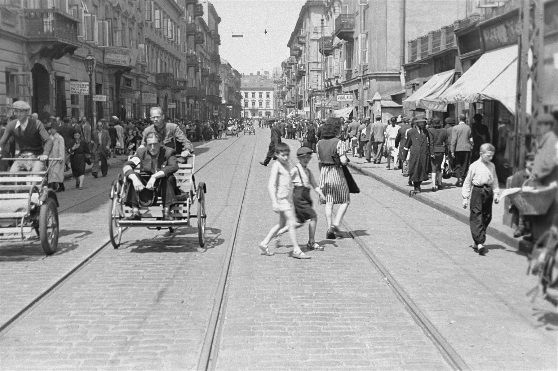 A Jewish man rides in a rickshaw on a crowded street in the Warsaw ghetto.