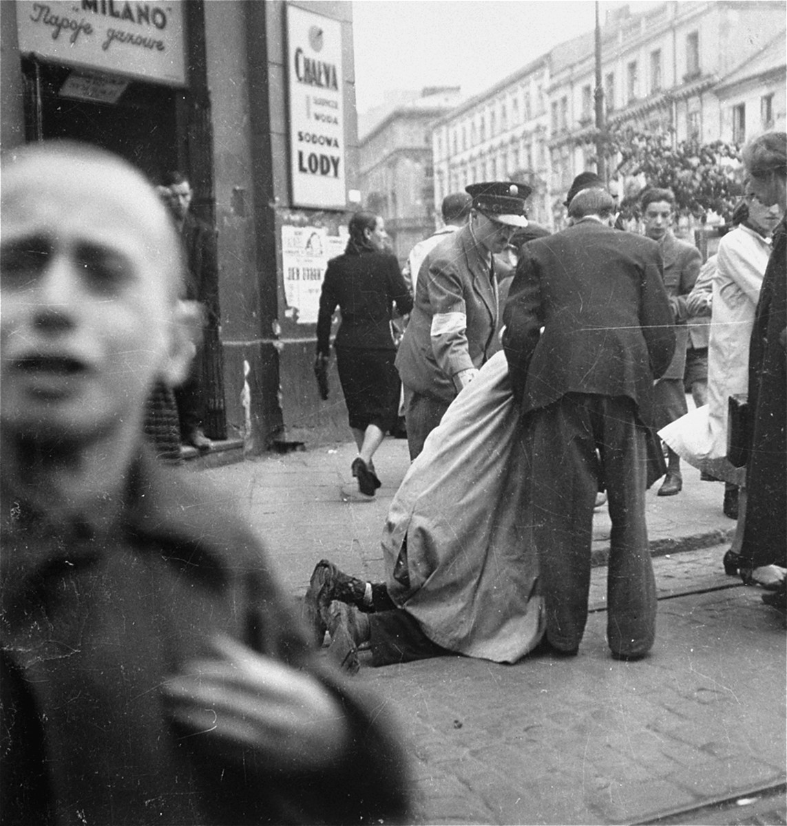 "A Jewish policeman and a pedestrian help an old man collapsed on the street in front of an ice cream shop.    Joest's caption reads: ""I had just arrived on the scene when an old man collapsed in front of an Italian ice shop.  Passersby and a Jewish policeman attempted to help him up."""
