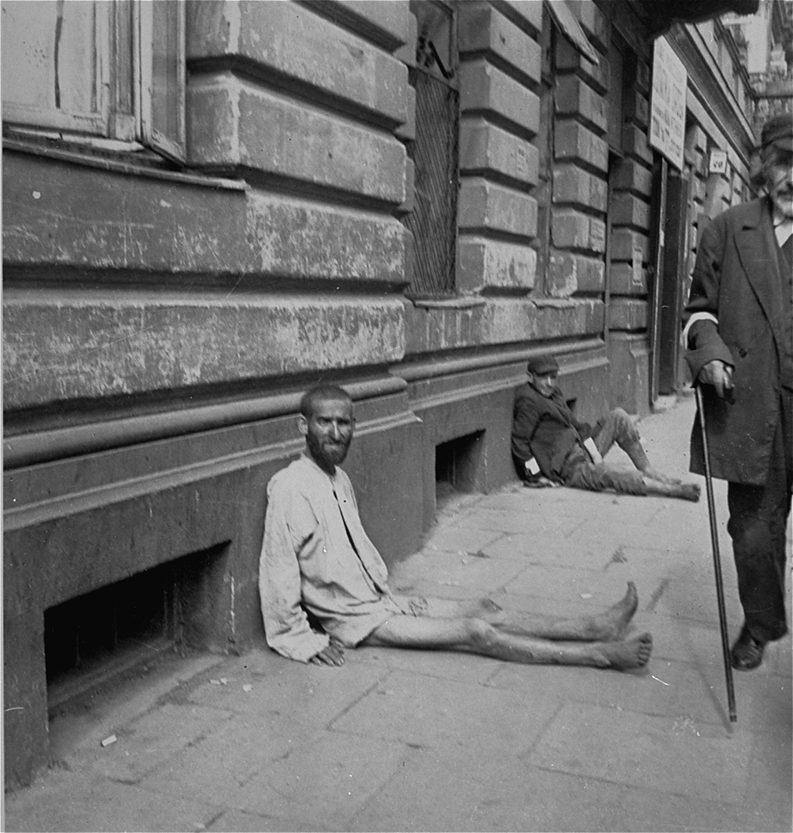"A destitute man wearing nothing but a shirt sits on the pavement near the street entrance to the Pinkiert funeral home in the Warsaw ghetto.    Joest's caption reads: ""On the street in front of the entrance to the funeral home sat beggars with only leather-like skin over their bones."""