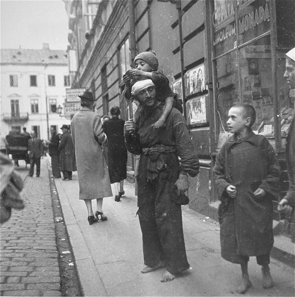 "A destitute Jewish man with his two children on a street in the Warsaw ghetto.   Joest's original caption reads: ""Next to a lady with a good coat and shoes that had heels, stood next to this broken-down man, barefoot, with his barefoot child on his shoulders."""