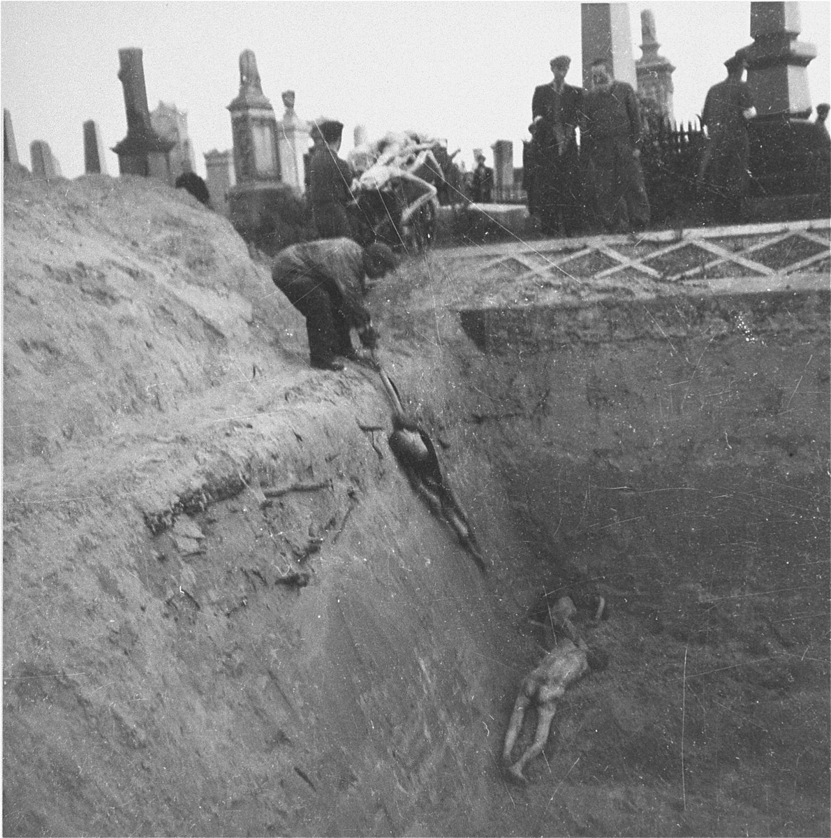 "Undertakers from the funeral home of M.B. Pinkiert unload bodies from a cart into a mass grave in the Warsaw ghetto cemetery.    Joest's caption reads: ""There were four men who carried the bodies from the cart to the grave, dropped them in and stacked them."""