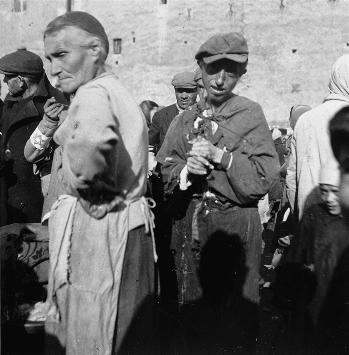 """A destitute Jewish man in the Warsaw ghetto wrings his hands after finishing a bowl of soup given to him in a public market by the woman at left.    Joest's caption reads: """"This other one had already eaten his soup, but did not look [as if his hunger was] satisfied."""""""