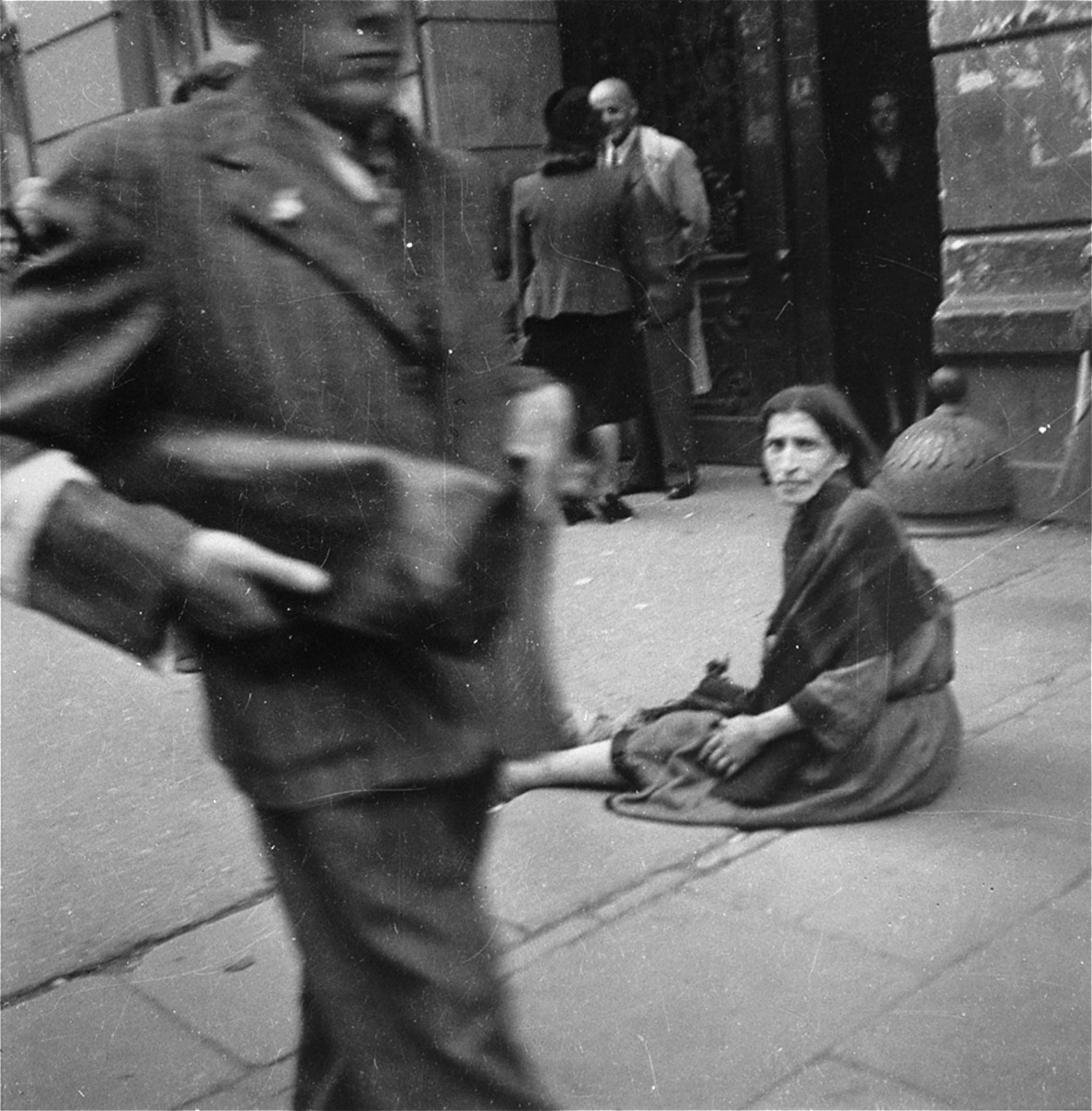 "A destitute woman sits in the middle of a busy sidewalk in the Warsaw ghetto.    Joest's caption reads: ""In the middle of the sidewalk sat this wailing woman, over whom no one troubled himself, and begged.  What was astounding was that from time to time she received something even though everything was going so badly with all the others as well."""