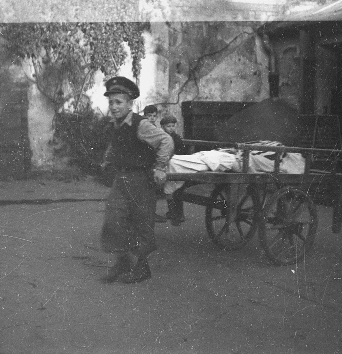 "A boy working in the Jewish cemetery on Okopowa Street pulls a body out of the morgue for burial.    Joest's caption reads: ""A child, surely not yet thirteen-years-old, pulled a cart laden with bodies [as] children of similar age watched him do it."""