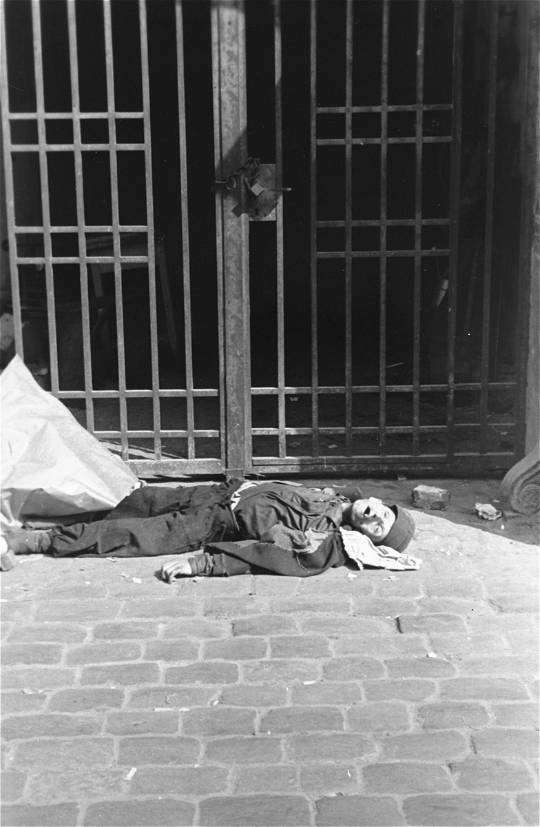 A man lies dead on the pavement at the entrance to a building in the Warsaw ghetto.