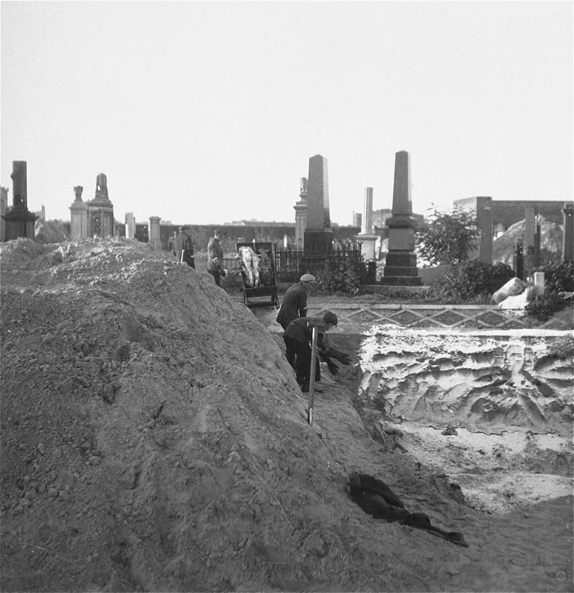 """Gravediggers unload bodies from a cart into a mass grave in the Warsaw ghetto cemetery.    Joest's caption reads: """"The corpse-carriers took the naked bodies from the cart and threw them into the grave.  For this work they wore rubber-gloves, which I first thought were made out of wood."""""""