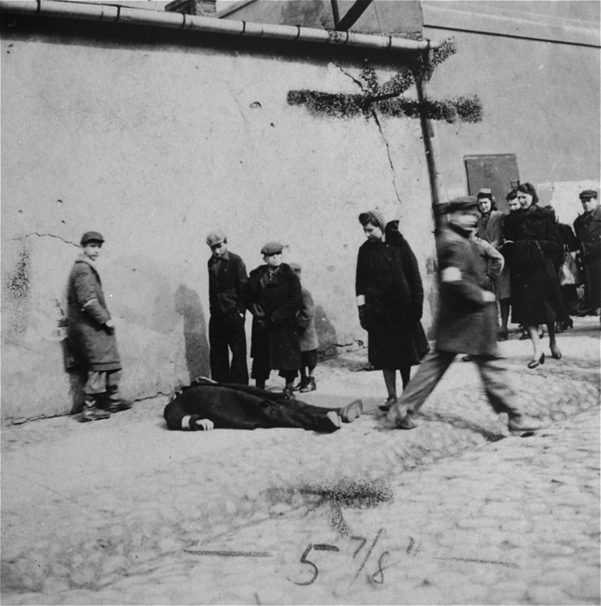Warsaw ghetto residents stare at a man who has collapsed in the street.