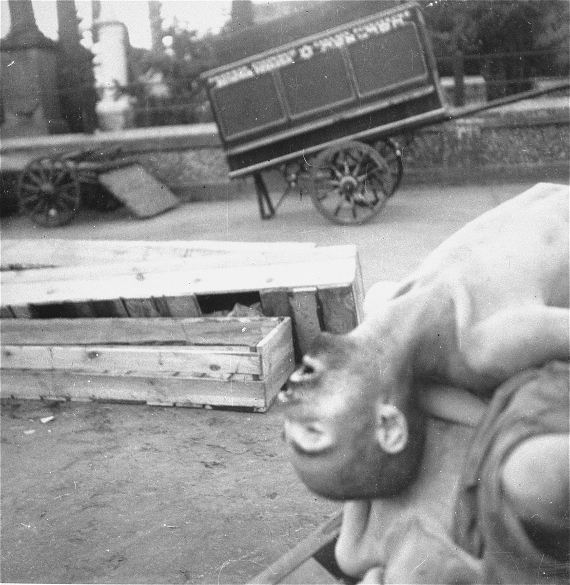 "Bodies, coffins, and a funeral wagon on the grounds of the Jewish cemetery on Okopowa Street in the Warsaw ghetto.    Joest's caption reads: ""I took this photo at the Jewish cemetery.  I do not understand today how I could have photographed something like this."""