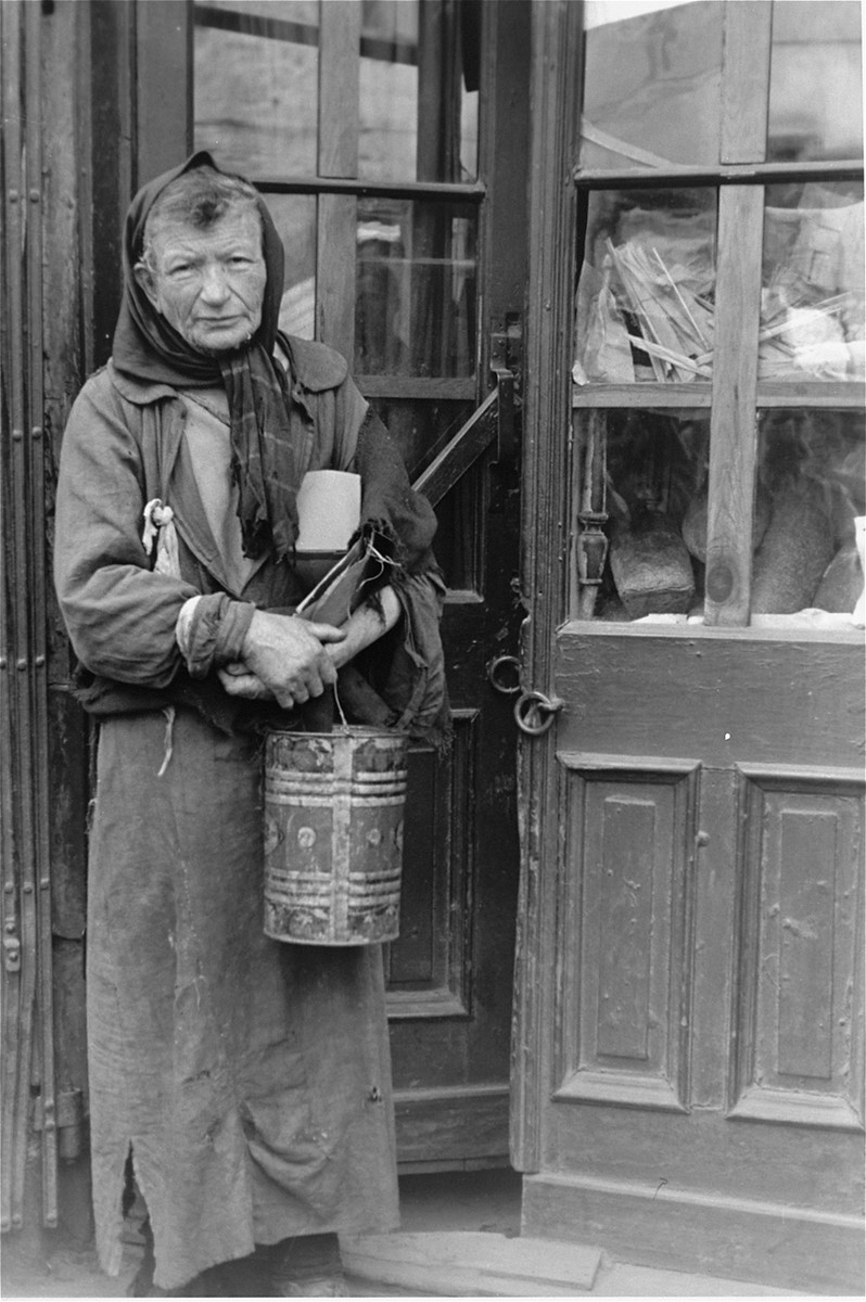 A destitute Jewish woman poses in the doorway of a store in the Warsaw ghetto holding a metal container.