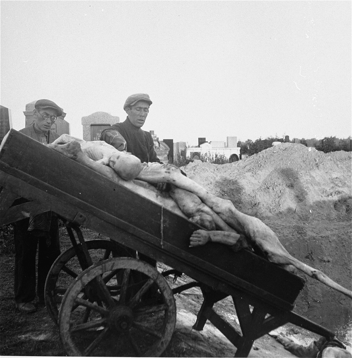 "Gravediggers unload bodies from a cart into a mass grave in the Warsaw ghetto cemetery.    Joest's caption reads: ""It was an enormous grave, into which cart after cart of bodies was tipped.  After [the bodies were in] the men spread lime chloride over them, and the grave was left open for the next cart."""