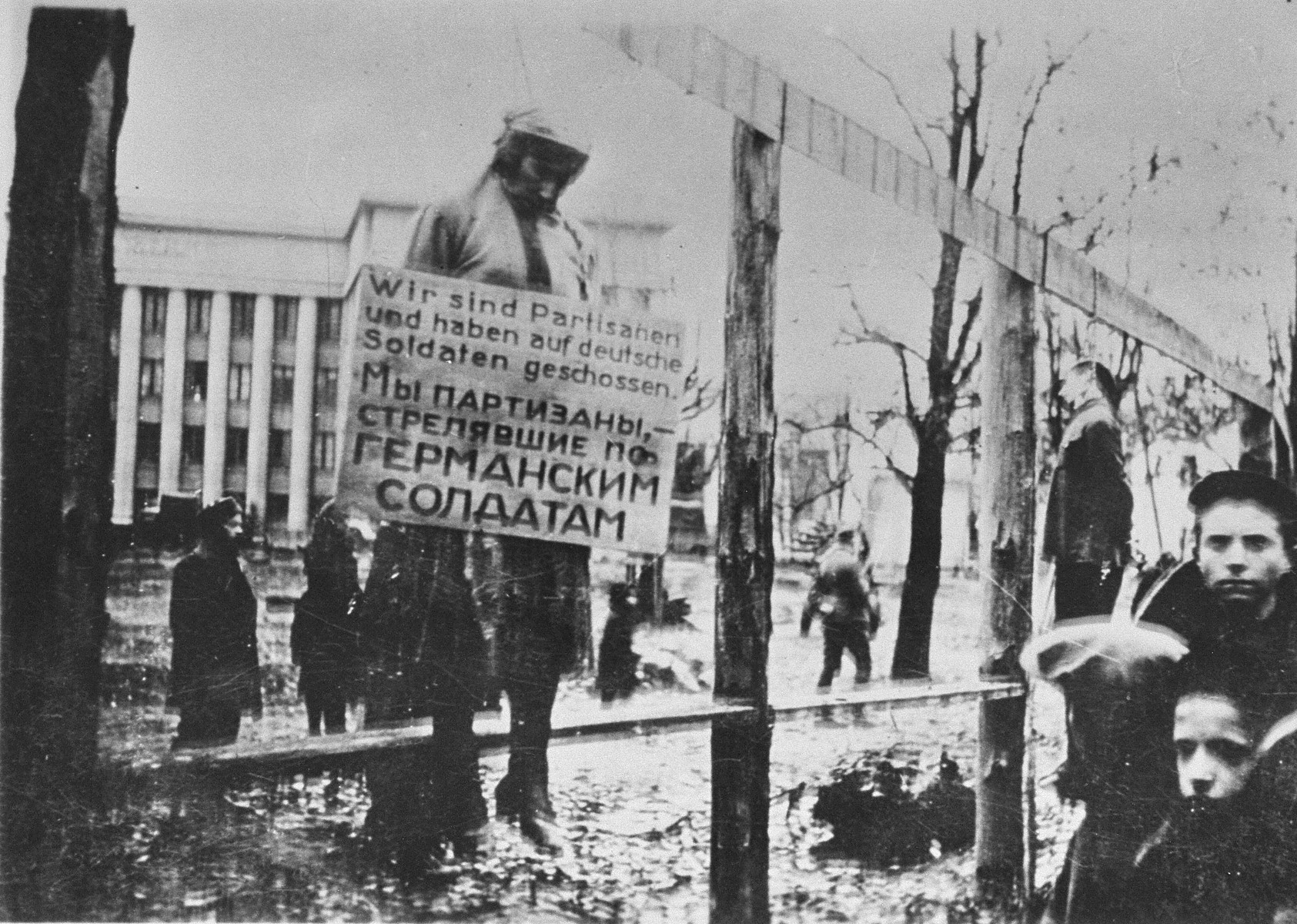 """The public hanging of three members of the Communist underground on Karl Marx Street in Minsk.  One of the victims wears a large placard around his neck that reads """"We are partisans and have shot at German soldiers.""""  This execution was one of four carried out in Minsk on 26 October 1941 by German troops with the 707th Infantry Division.  Altogether, twelve members of the Communist underground were publicly hanged in four groups of three near a yeast-making factory.  This is believed to be the first public execution after the German invasion of the Soviet Union and it included the hanging of Masha Bruskina, a young Jewish woman.  In each of the four cases, the bodies were left to hang for several days to serve as a warning to would-be resisters."""