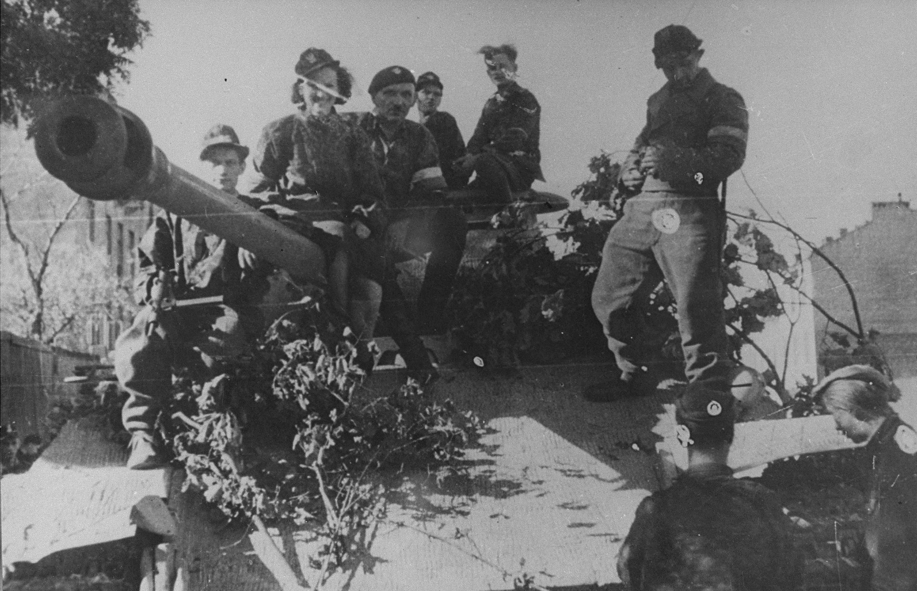 Members of the Zoska battalion of the Armia Krajowa stand atop a German tank captured during the 1944 Warsaw Uprising.    The tank was used by the battalion during its capture of the Gesiowka concentration camp.
