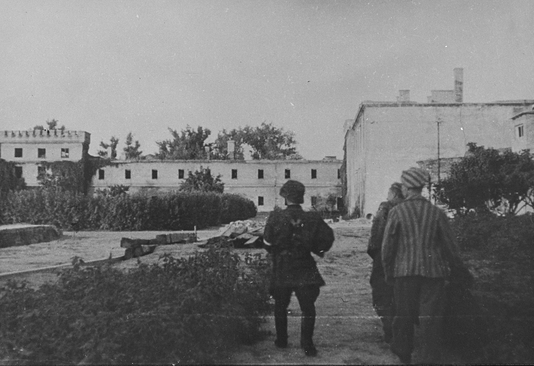 A member of the Zoska battalion of the Armia Krajowa escorts two of 348 Jews liberated from the Gesiowka concentration camp by the battalion, during the 1944 Warsaw Uprising.