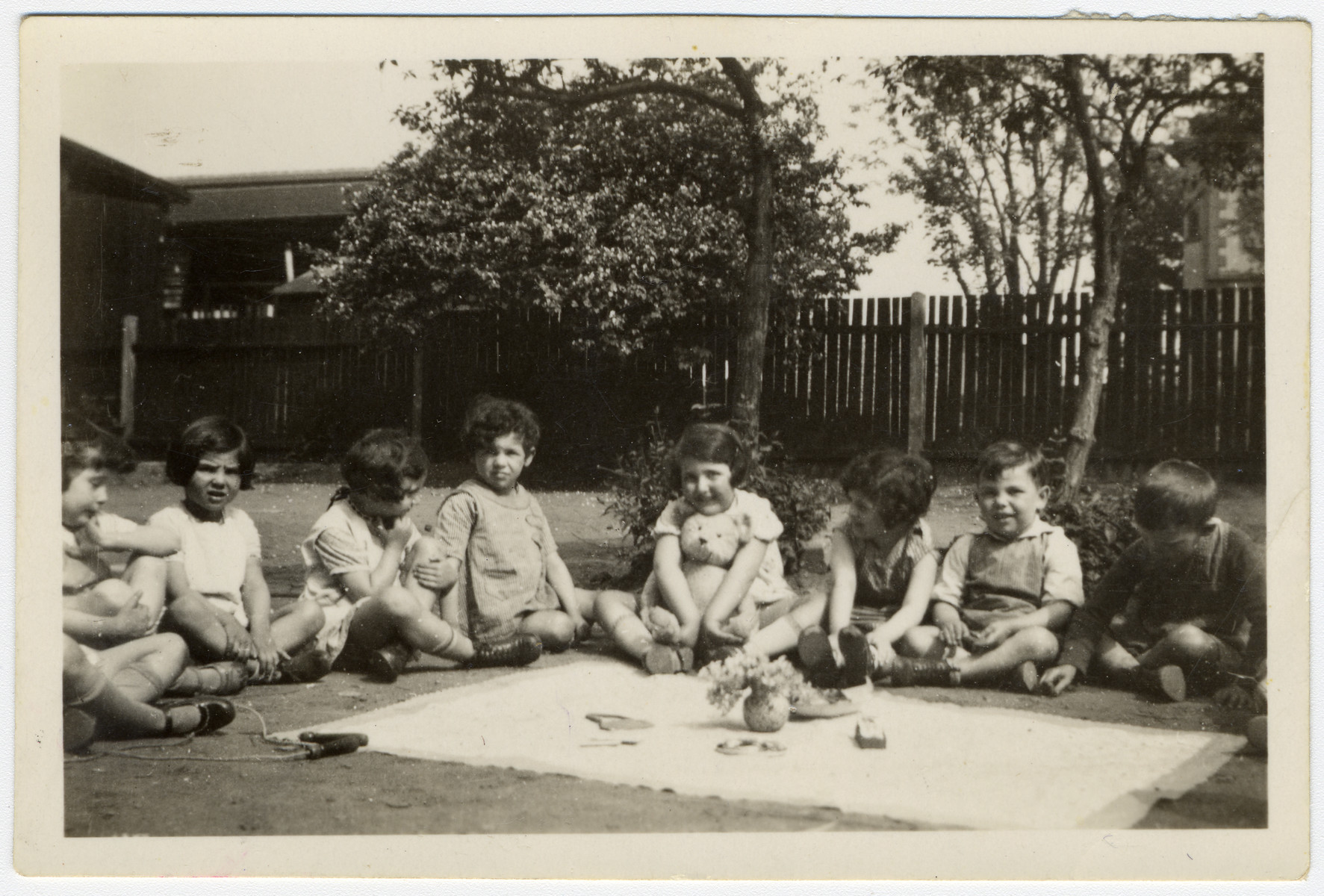 Children in a Mannheim preschool sit outside on the lawm.  Margot Schumm is seated in the center, holding a teddy bear,