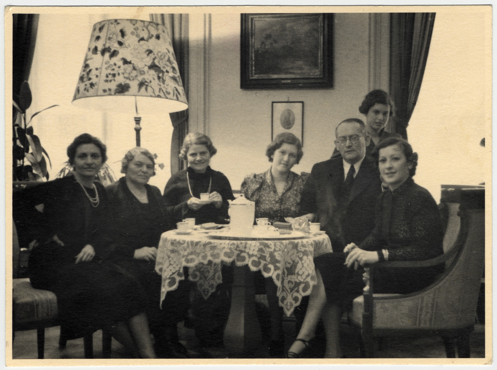 A Jewish family in Czechoslovakia poses by a table laden with coffee cups on the wedding day of their daughter, Lotte Aldor (the cousin of the donor).  Pictured from left to right are Marianne Aldor (the mother of the bride), Gusti Aldor, Emmy Aldor (sister of Marianne), Lotte Aldor, Robert Ayer, Mimi (Lotte's sister) and unidentified.