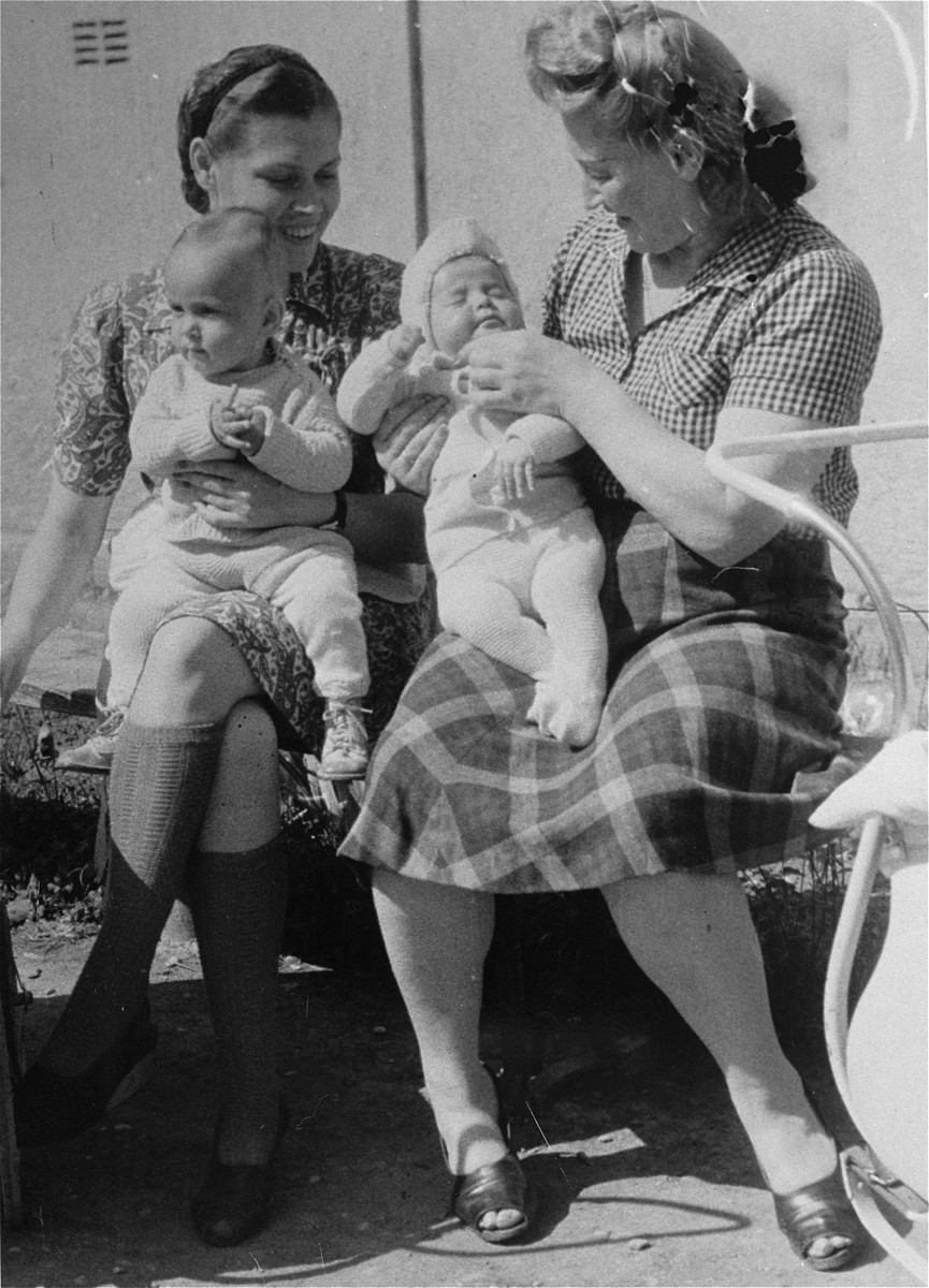 Two women sit in the sun with their babies at Bindermichl DP camp.  Among those pictured is Herta Getzler (nee Nussbaum) with her son, George Getzler. Herta gave birth in the DP camp in Linz.