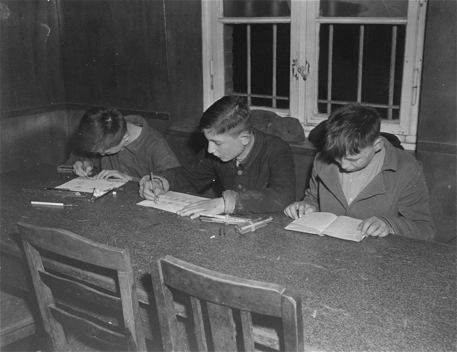 Three young survivors study at a table in the Hadamar Institute.  The photograph was taken by an American military photographer soon after the liberation.