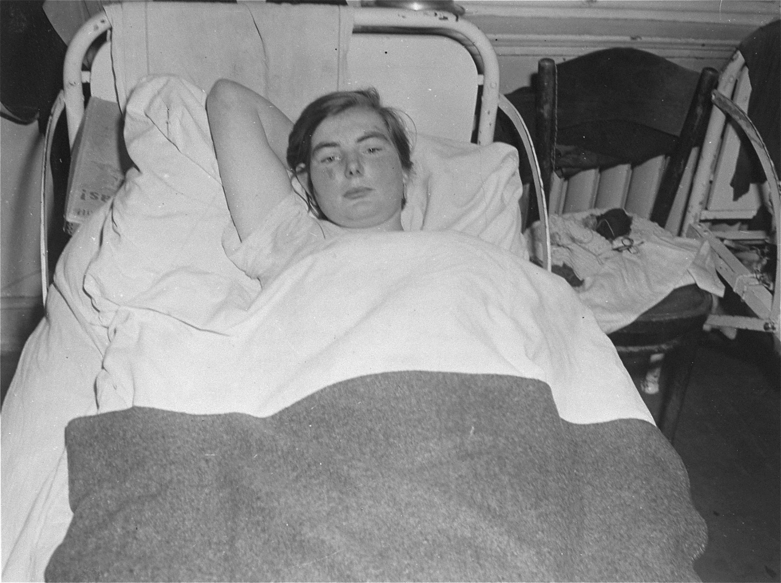 A female survivor lies in bed at the Hadamar Institute.  23-year-old Elizabeth Killiam, the mother of twins, was sterilized at a health care facility in Weilburg before being transferred to the Hadamar Institute.  The photograph was taken by an American military photographer soon after the liberation.