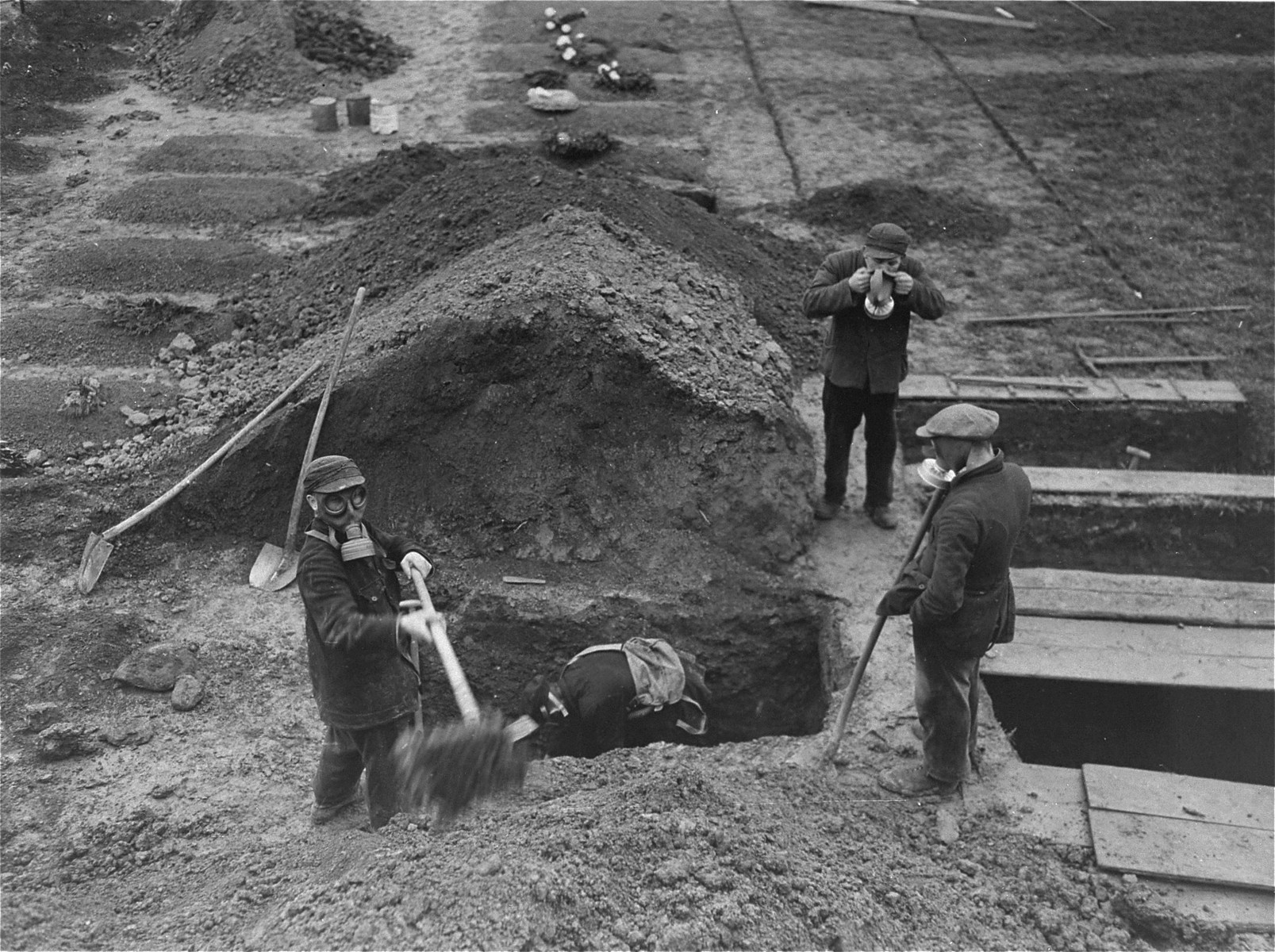 German civilians exhume the bodies of 44 Polish and Russian forced laborers who were put to death at the Hadamar Institute and buried in a mass grave behind the euthanasia facility.    The grave was opened at the direction of American war crimes investigators.  The photograph was taken by an American military photographer soon after the liberation.