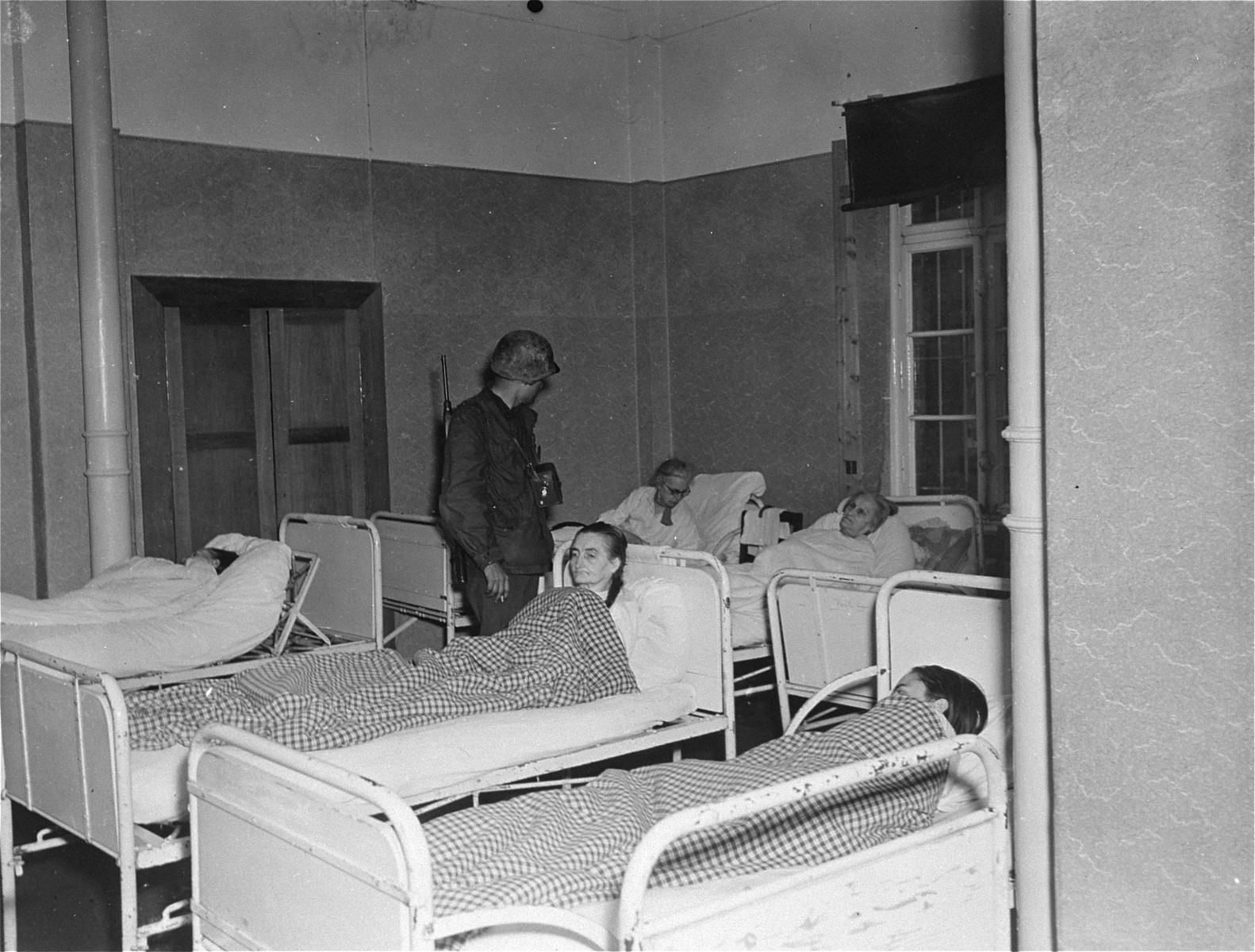 Lt. Alexander J. Wedderburn, photographer with the 28th Infantry Division, First US.Army, questions elderly survivors who are lying in bed at the Hadamar Institute.   The photograph was taken by an American military photographer soon after the liberation.