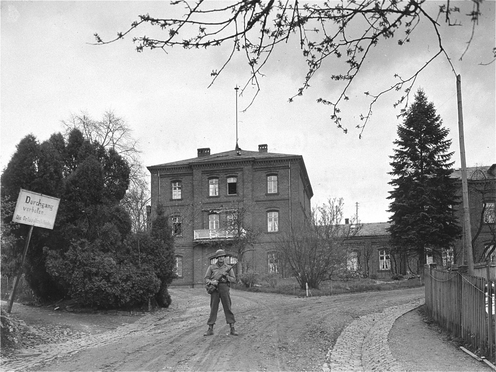 An American sentry stands guard in front of the Hadamar Institute.  The photograph was taken by an American military photographer soon after the liberation.