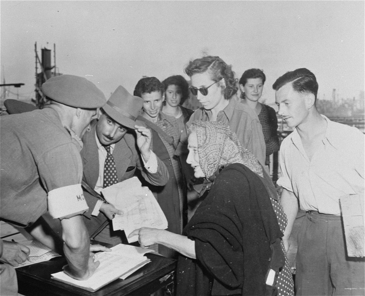 Jewish displaced persons fill out papers in the presence of British soldiers, prior to boarding ships for Palestine.