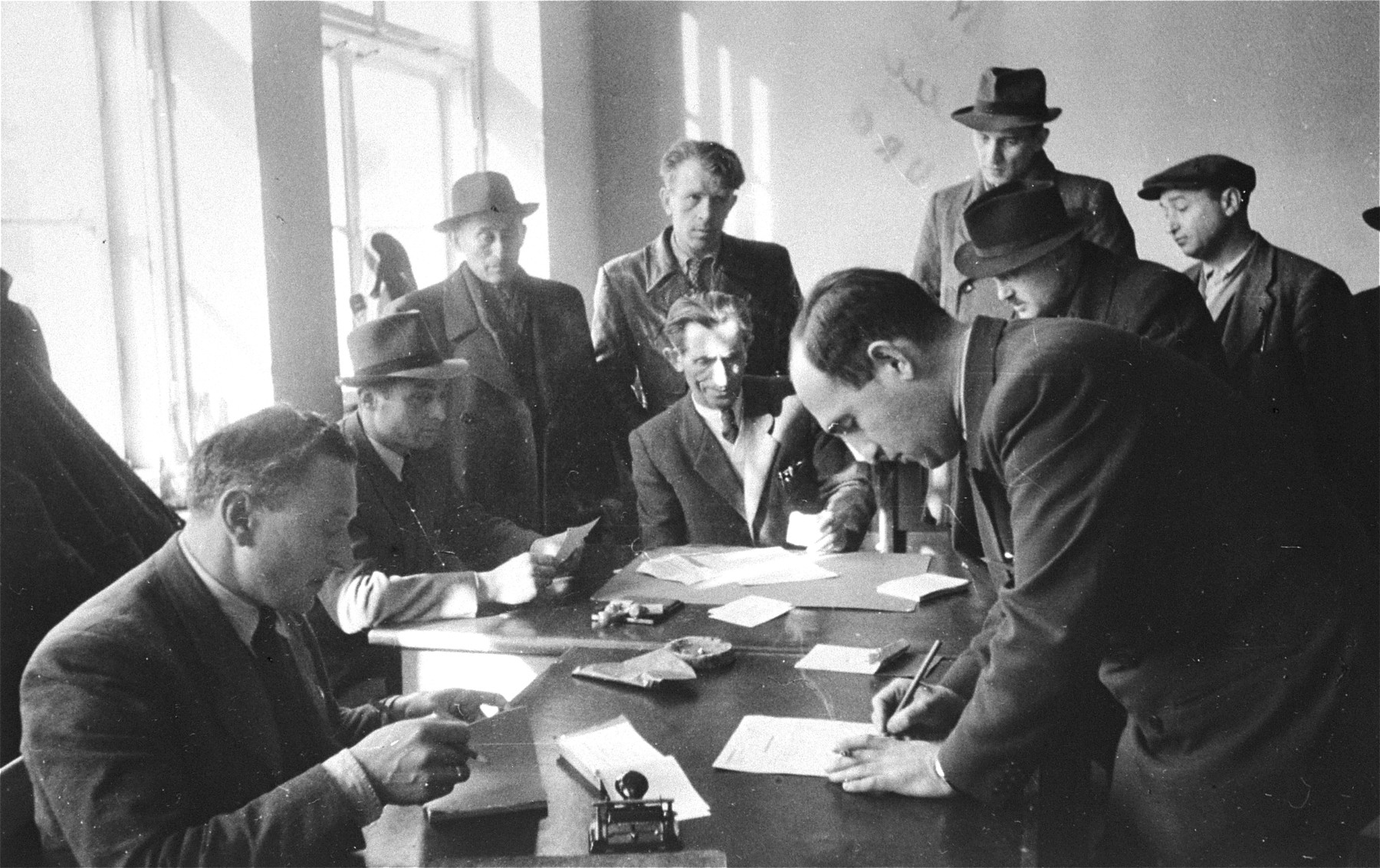 Departing DPs from the Bergen-Belsen camp sign emigration documents.  The DPs are on their way to Palestine.