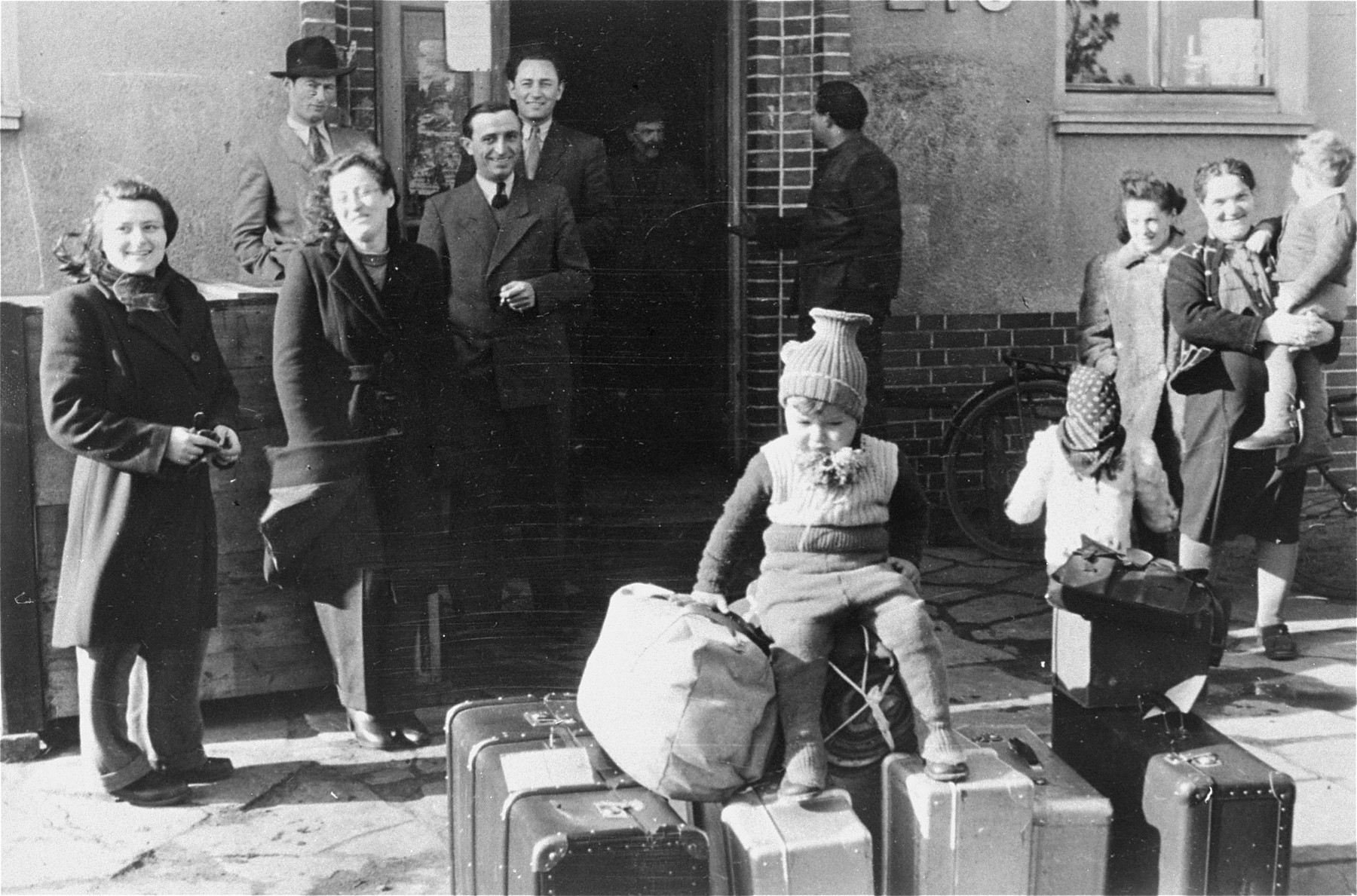 Departing DPS from the Bergen-Belsen camp wait with their luggage in front of their living quarters.  The DPs are on their way to Palestine.