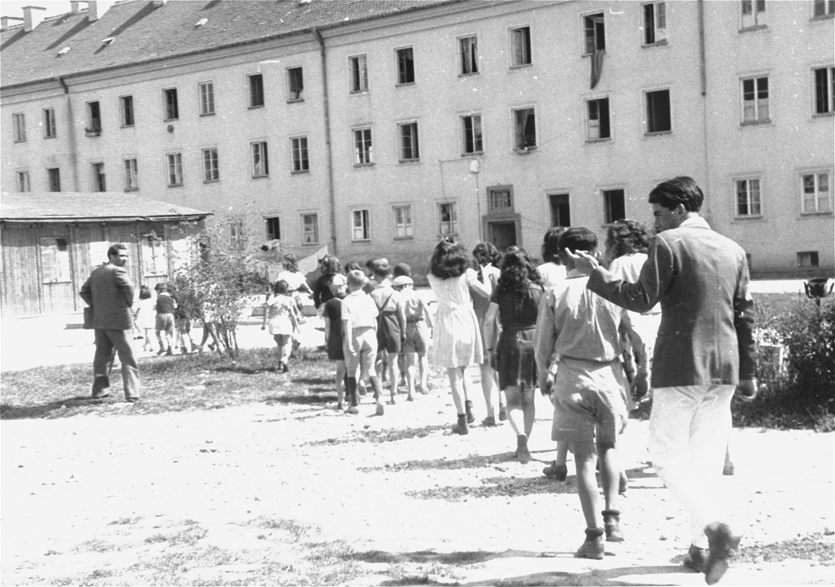 Children walk toward the food distribution building in Bindermichl DP camp.  Pictured on the far left with is back to the camera is Hersch Biederman, who worked at the food distribution warehouse.