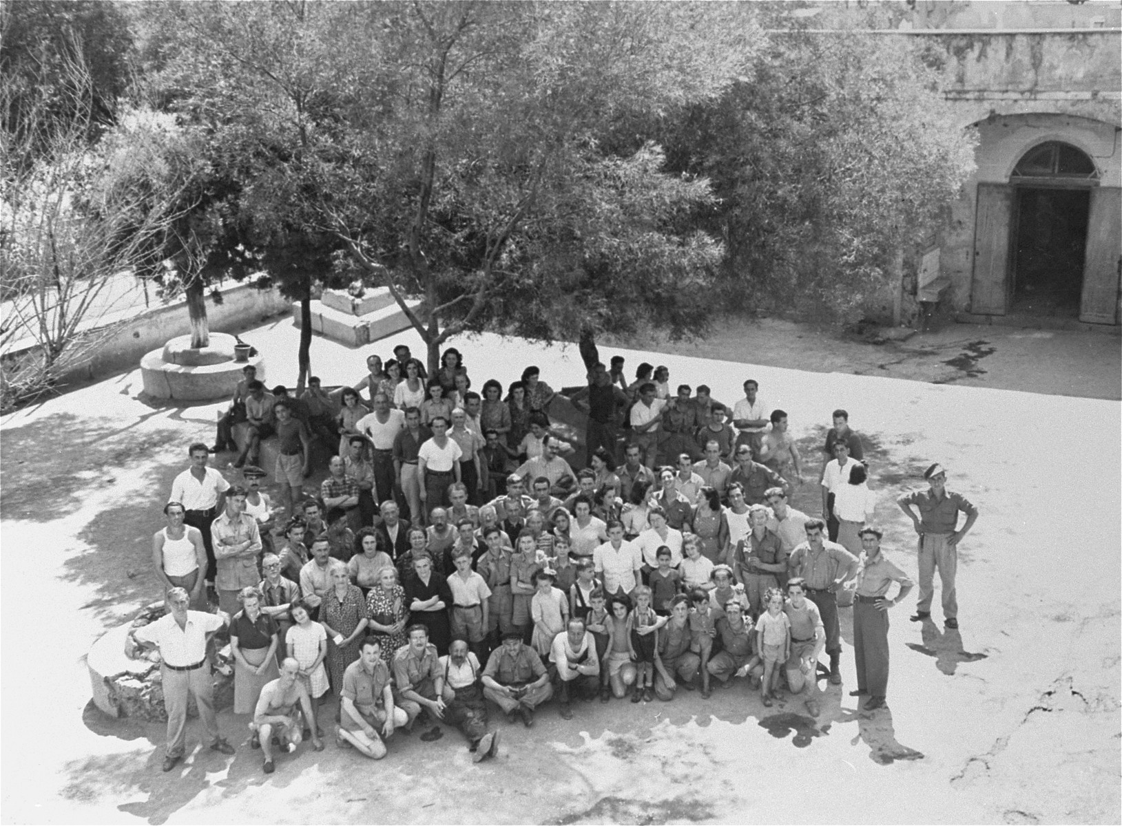 Group portrait of Jewish DPs who have trained at an hachshara in Italy awaiting transport to Palestine.