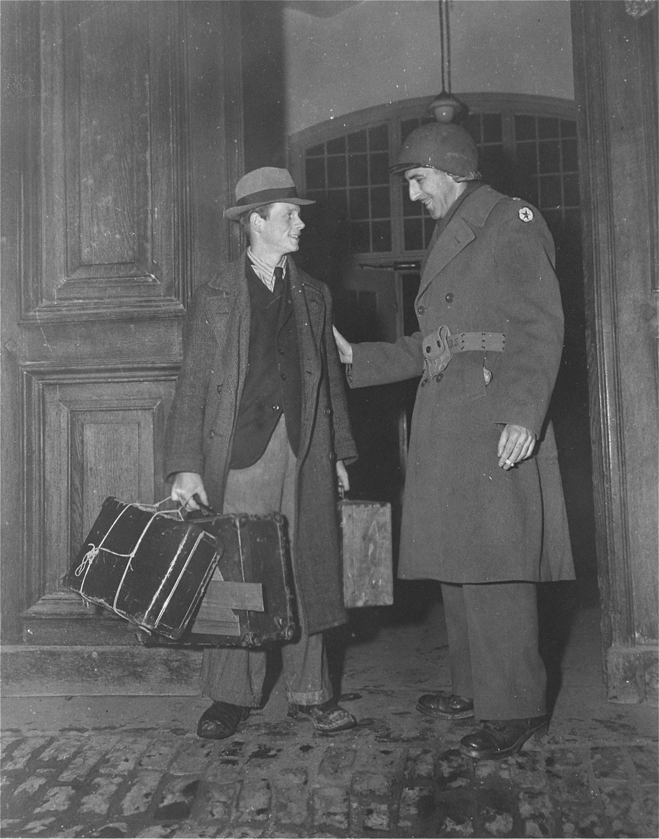 A survivor who is leaving the Hadamar Institute bids farewell to Major Herman Bolker, a member of the war crimes investigation tam at the former euthanasia facility.    The survivor had been committed to Hadamar for his anti-Nazi views.  The photograph was taken by an American military photographer soon after the liberation.