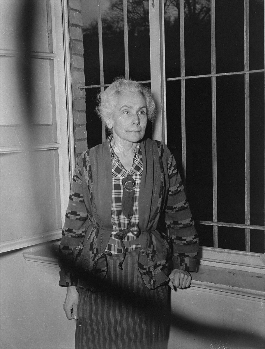 An elderly female survivor poses in front of a barred window at the Hadamar Institute, where she was imprisoned for writing anti-Nazi articles.  The photograph was taken by an American military photographer soon after the liberation.