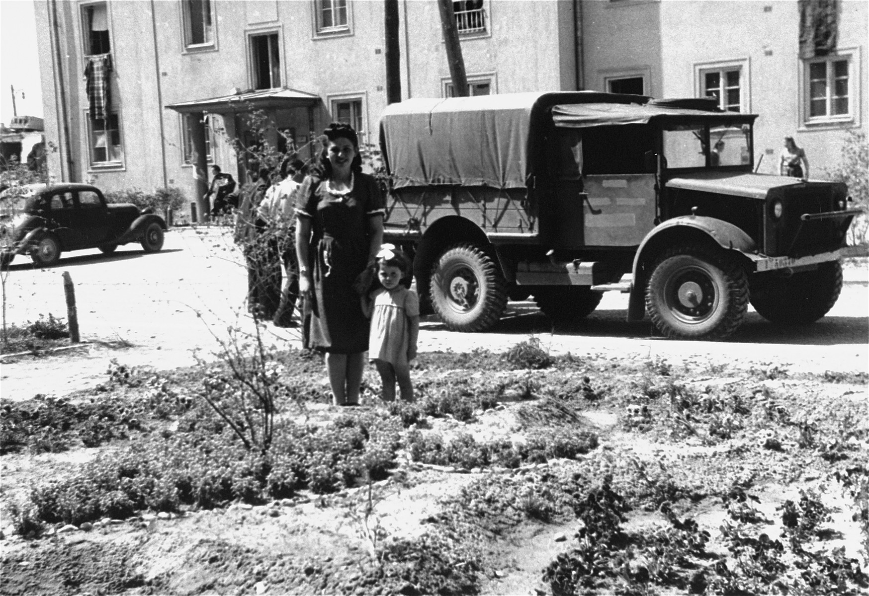 A woman and child, both DPs, stand in front of a military truck in Bindermichl DP camp.