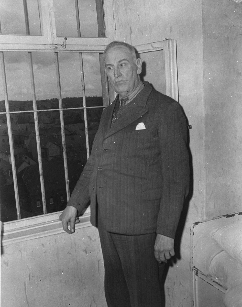 Dr. Adolf Wahlmann, chief physician at the Hadamar Institute, poses next to a barred window at the euthanasia facility where he is being held prisoner by American authorities.  The photograph was taken by an American military photographer soon after the liberation.
