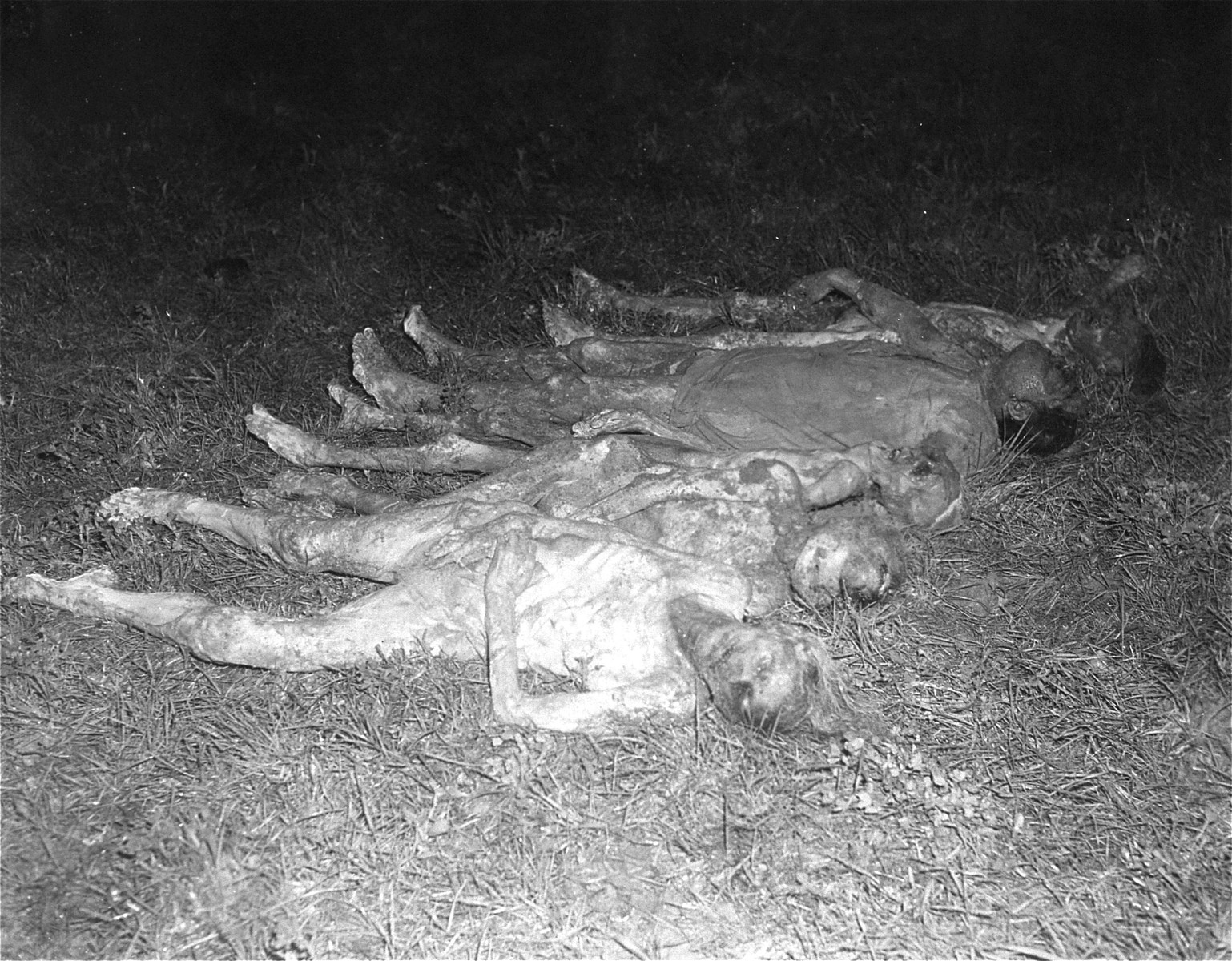 View of the exhumed bodies of Polish and Russian forced laborers who were put to death at the Hadamar Institute and buried in a mass grave behind the euthanasia facility.  The grave was opened at the direction of American war crimes investigators. The photograph was taken by an American military photographer soon after the liberation.
