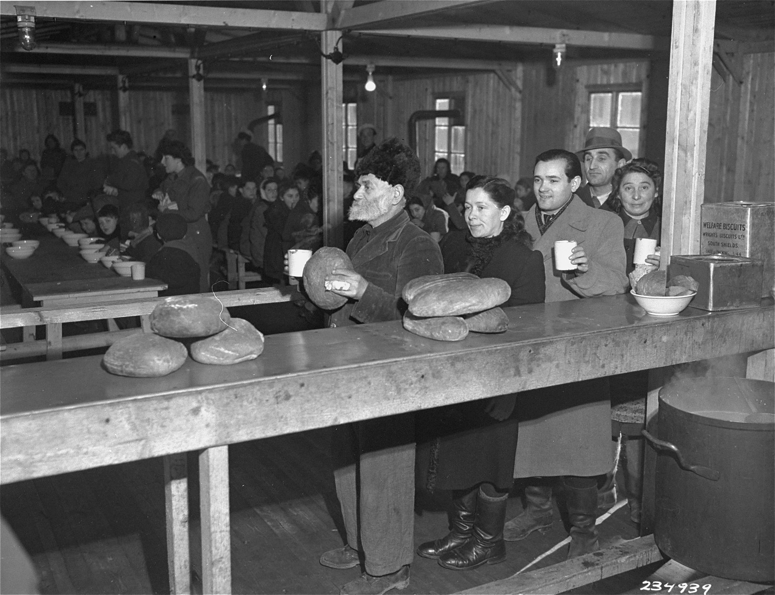 Jewish displaced persons receive bread rations at the Bindermichl displaced persons' camp in Linz.  Pictured are Esther and Sam Schlachtman.
