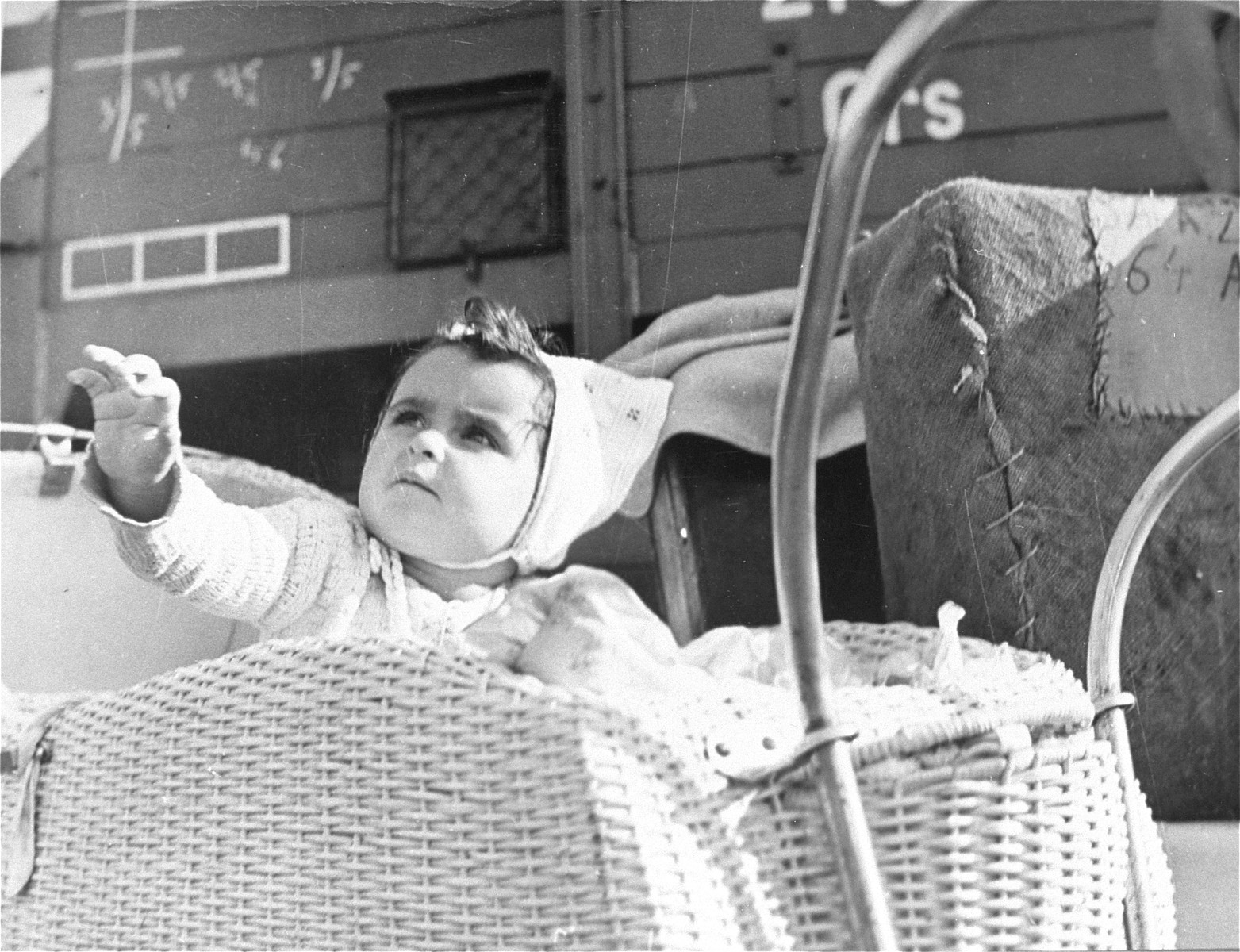 A baby waits in front of a train that will soon make the first leg of the trip from Germany to Israel.