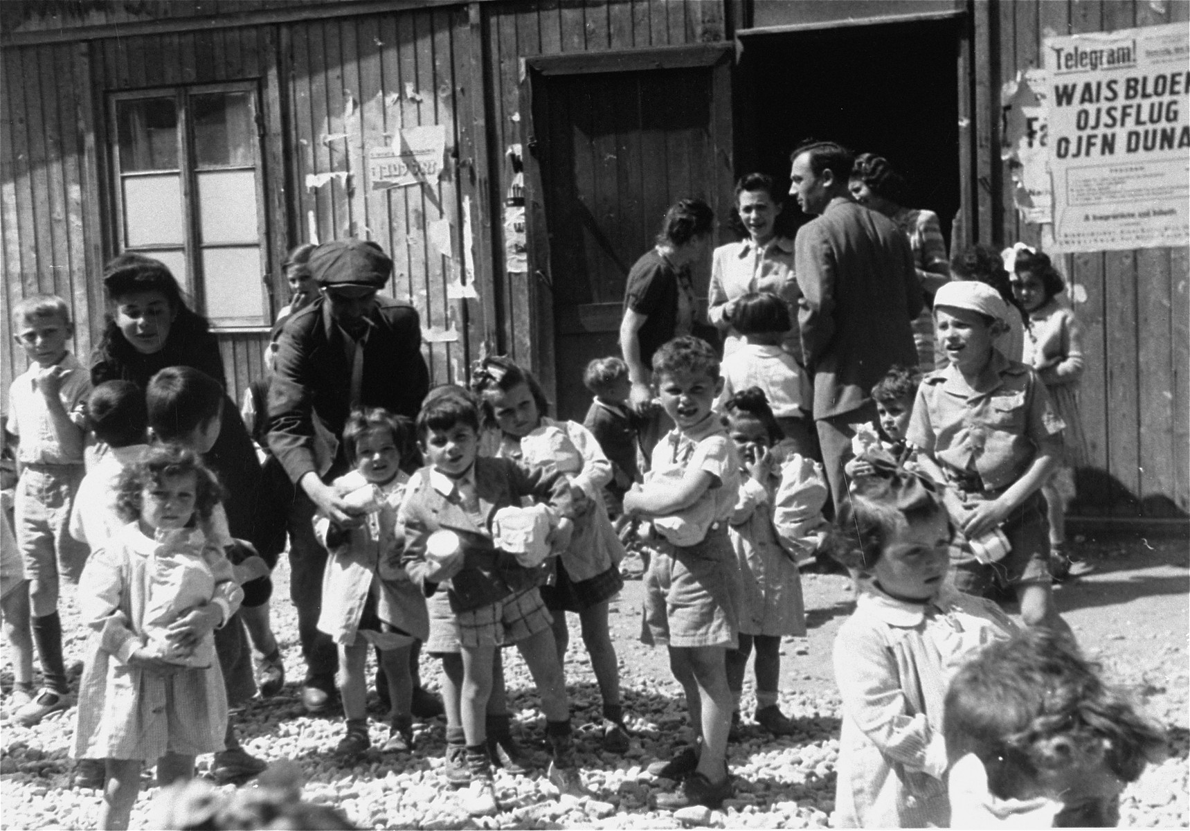Children stand in front of the food distribution building in Bindermichl DP camp.