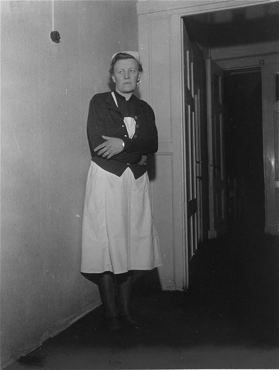Irmgard Huber, chief nurse at Hadamar Institute, poses in the corridor of the euthanasia facility.  The photograph was taken by an American military photographer soon after the liberation.