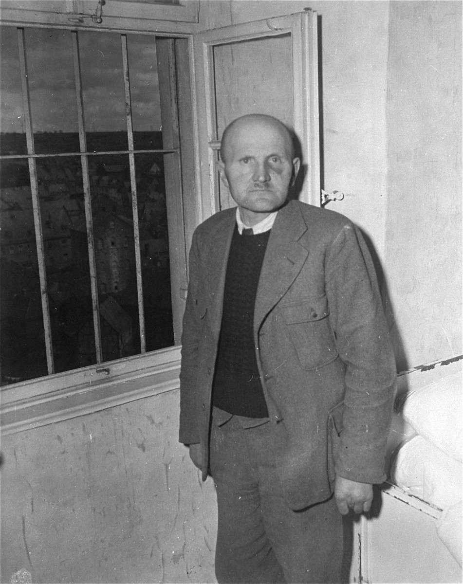 Karl Willig, assistant male nurse at the Hadamar Institute, poses next to a barred window at the euthanasia facility where he is being held prisoner by American authorities.  The photograph was taken by an American military photographer soon after the liberation.