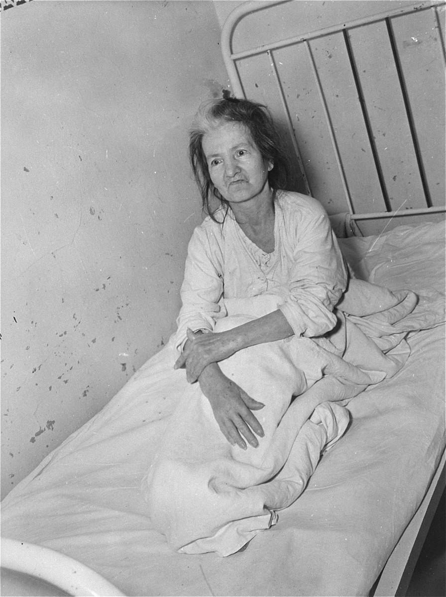 A female survivor lies in bed at the Hadamar Institute.    Pictured is Margaret Mann, the German common-law wife of Peter A. Klassen, an American World War I veteran, whom she met in Germany in 1918.  Their son was imprisoned elsewhere in Germany during World War II.  The photograph was taken by an American military photographer soon after the liberation.