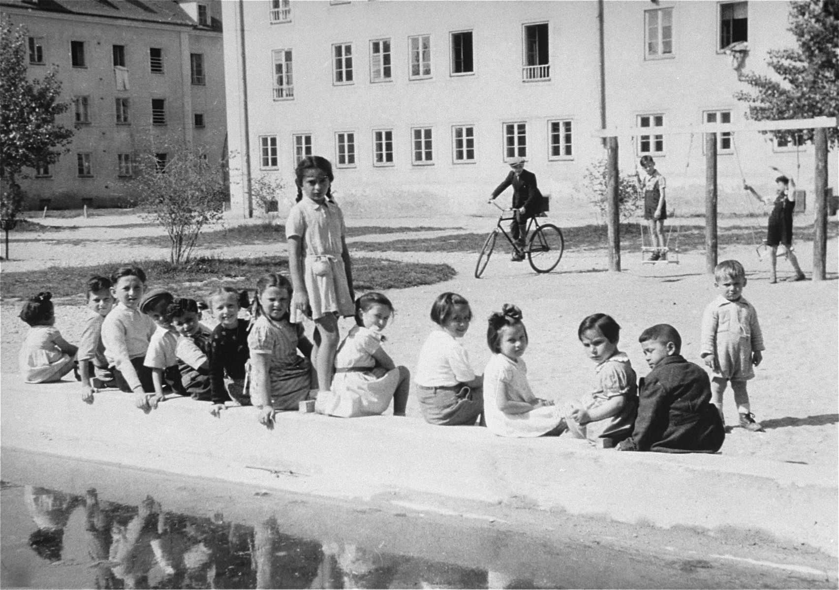DP children on the playground in the Bindermichl DP camp.    The first name of the girl standing in the center is Gittela (last name unknown).  The seated child directly to the left of the standing girl is Fayge Katz  (later Frances Schwartz).  She was born in Trochenbrod to Sara (Szames) Katz.  Sara later married Chaim Fisgeyer, while in Bindermichl, and they had a daughter named Mona.