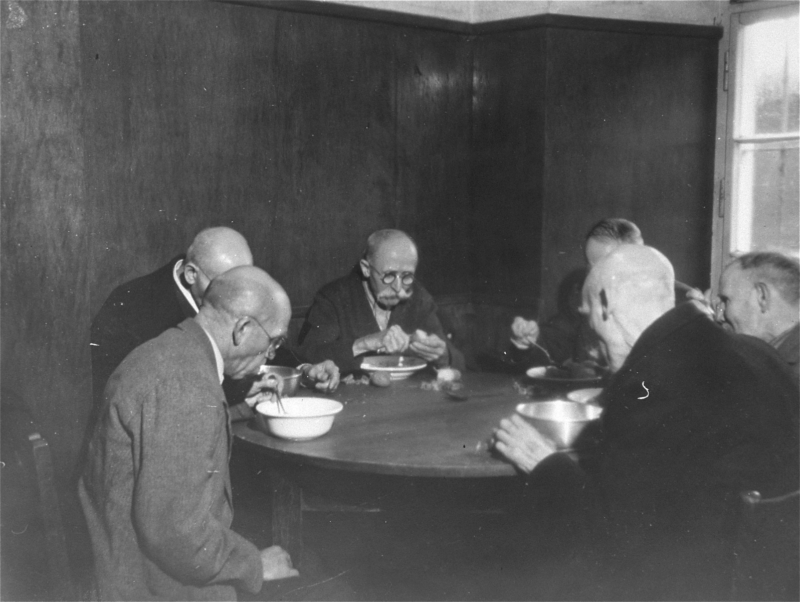 A group of elderly survivors eat a hearty meal at the Hadamar Institute after war crimes investigators demanded they be given larger rations.   The photograph was taken by an American military photographer soon after the liberation.