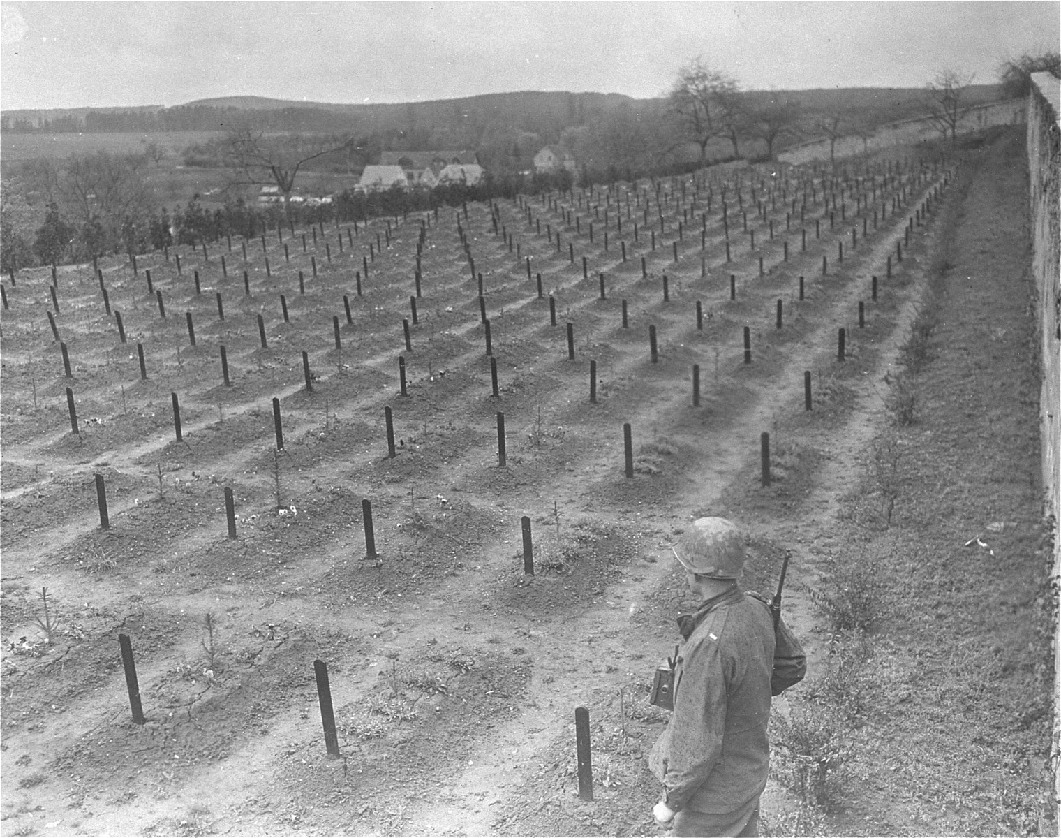 Lt. Alexander J. Wedderburn, photographer with the 28th Infantry Division, First US Army, views the cemetery at the Hadamar Institute, where victims of the Nazi euthanasia program were buried in mass graves.  The photograph was taken by an American military photographer soon after the liberation.