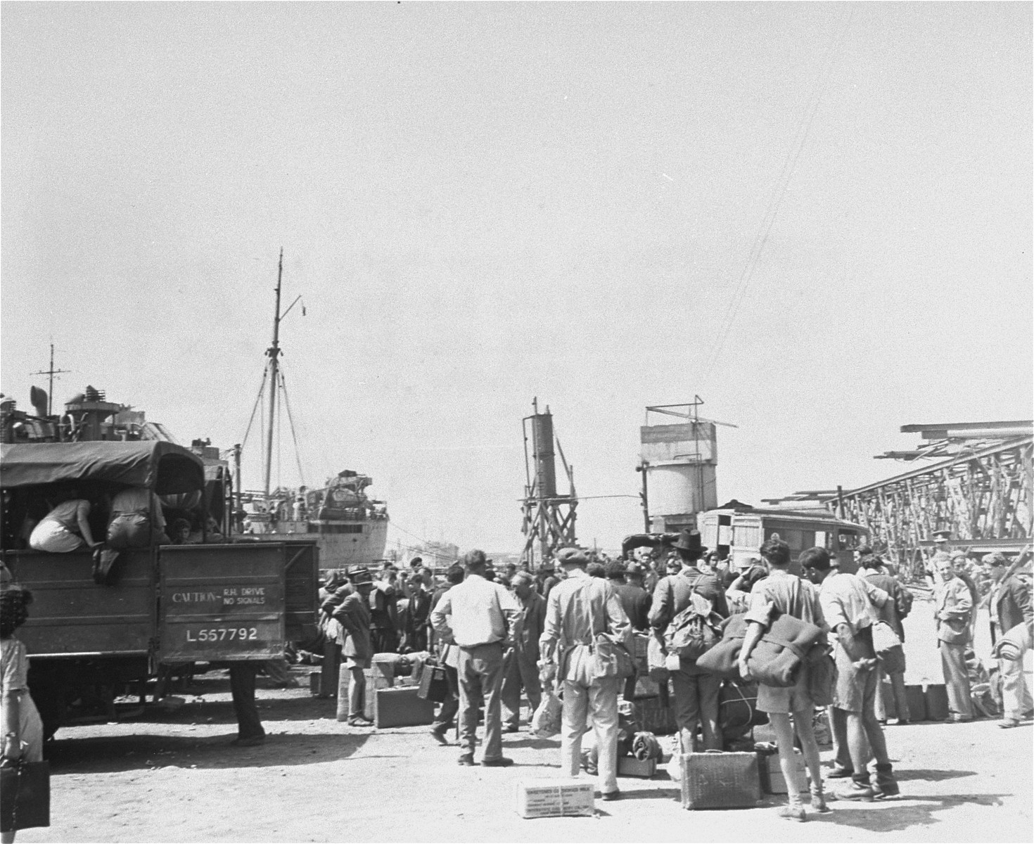 Jewish displaced persons assisted by members of American Joint Distribution Committee staff wait  to board a ship bound for Palestine.