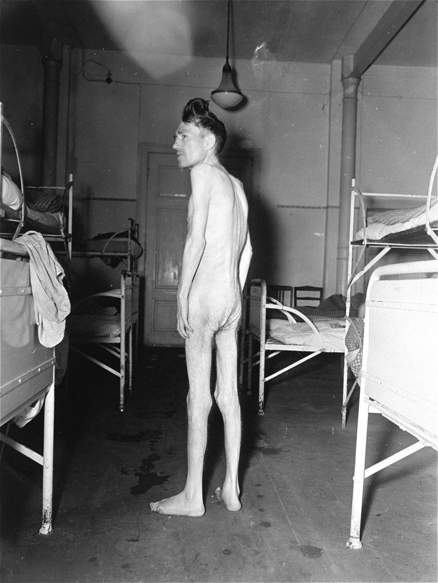 An emaciated survivor stands naked between rows of beds at the Hadamar Institute.  The photograph was taken by an American military photographer soon after the liberation.