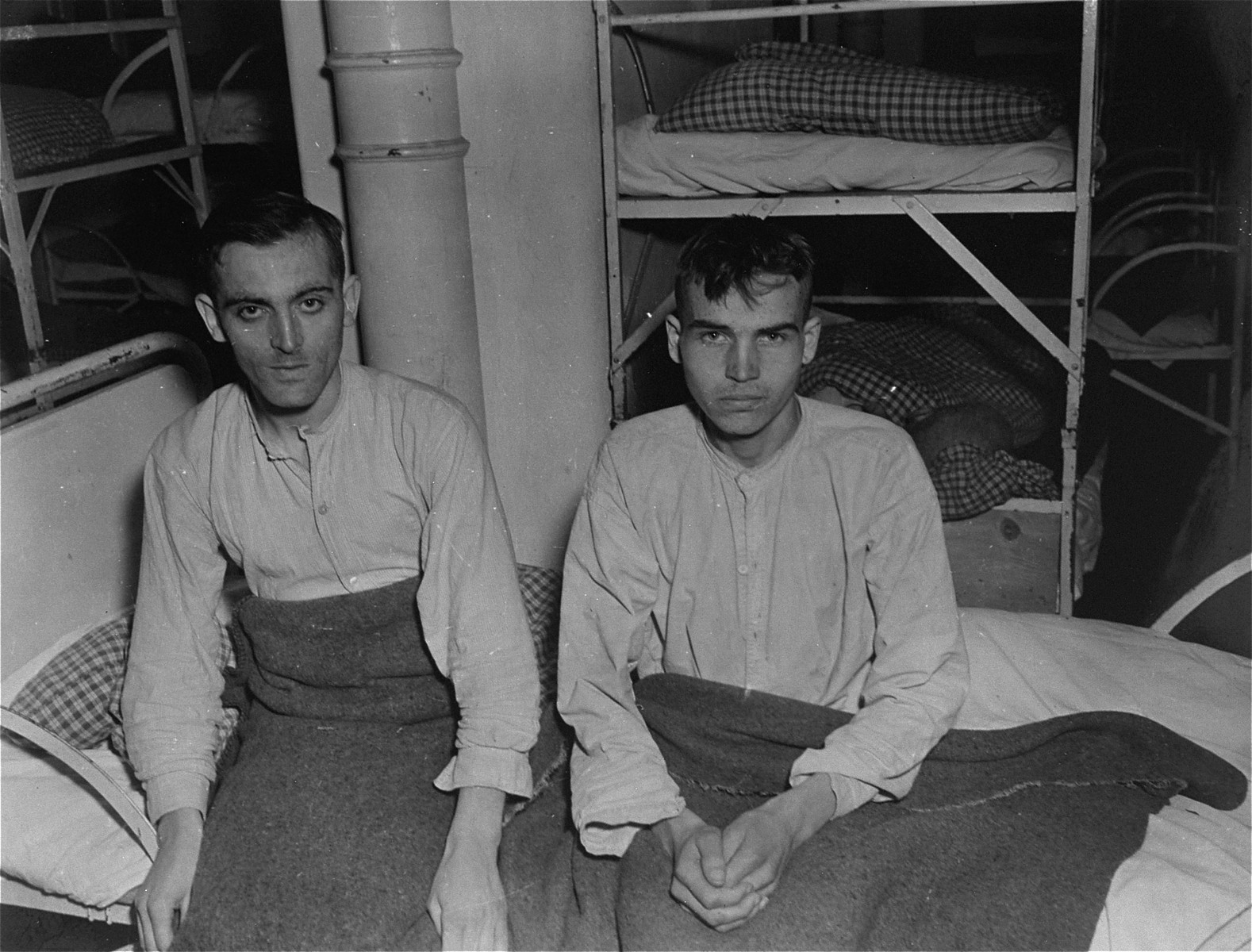 Two SS survivors of the Hadamar Institute sit on a bed at the former euthanasia facility.   These German SS had been committed to Hadamar after suffering mental breakdowns in the last year of the war.  The photograph was taken by an American military photographer soon after the liberation.
