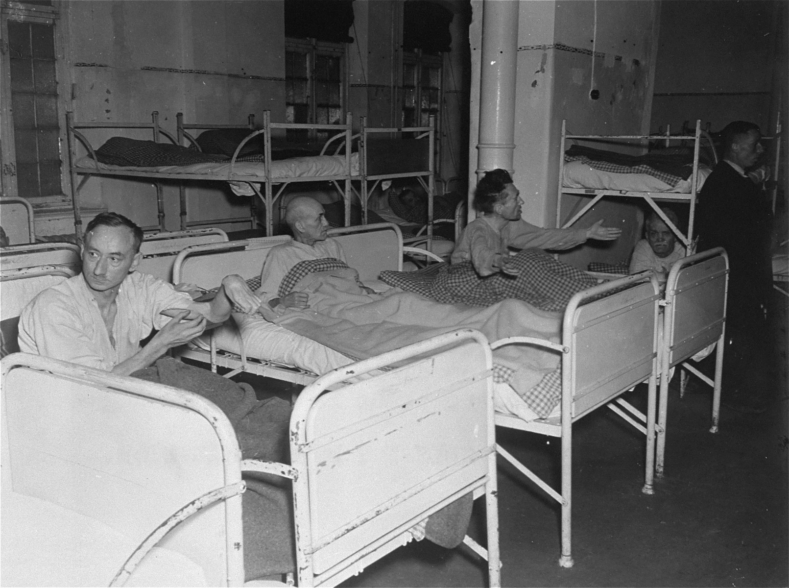 Three survivors rest in their beds at the Hadamar Institute.  The photograph was taken by an American military photographer soon after the liberation.