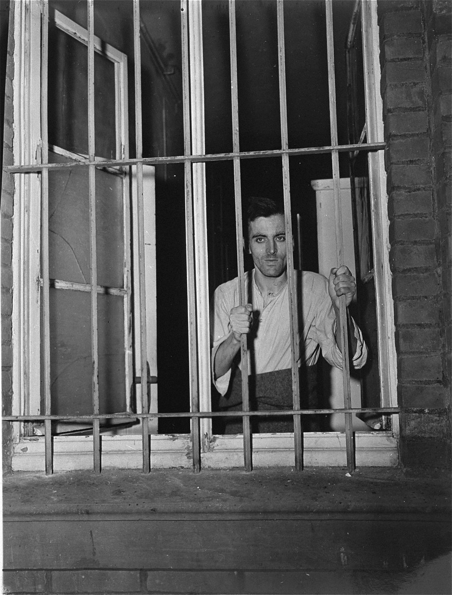 A survivor looks out a barred window at the Hadamar Institute.  The photograph was taken by an American military photographer soon after the liberation.